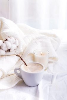 Bedding with a fluffy knitted plaid and cup of coffee, cotton flowers and candle.