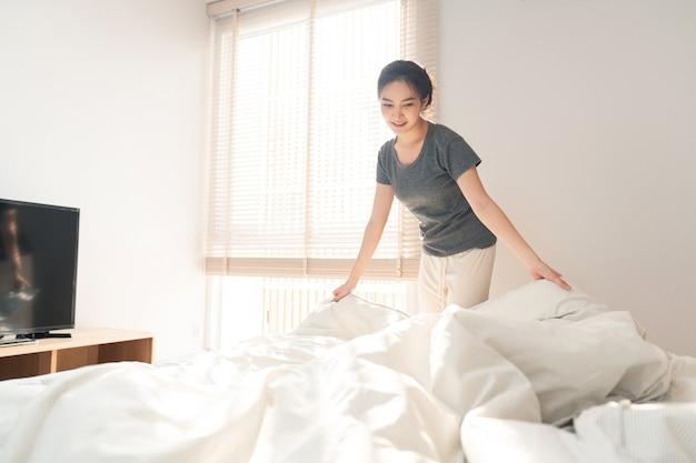 Концепция спальни: взрослая женщина делает рутину, хватаясь за край одеяла, чтобы застелить постель после пробуждения утром.