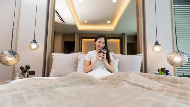 寝室のコンセプト彼女の寝室でその匂いに深呼吸をしている両手で熱い飲み物の警官を保持している長い髪の少女。