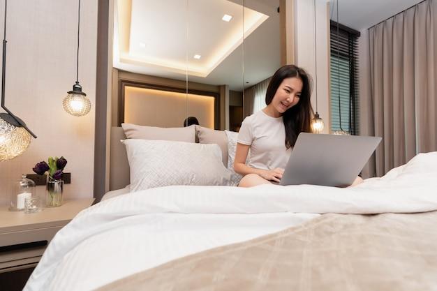 아늑한 분위기의 침실에 있는 침실 개념은 온라인 작업을 위해 노트북을 사용하여 큰 담요를 깔고 침대에 앉아 있는 소녀입니다.