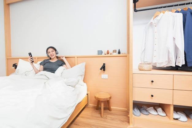 Концепция спальни на удобной кровати девушка слушает свои любимые песни в наушниках по утрам.