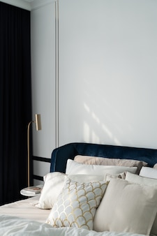 Bedroom corner navy blue velvet bed with soft pillows setting decorated with circular marble night table and navy blue paint wall