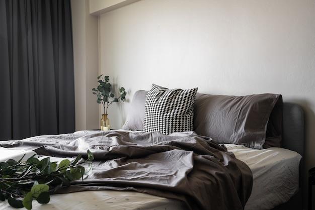 Спальня с мягкими подушками, украшенная круглым ночным столиком и золотой рамкой на бежевой крашеной стене