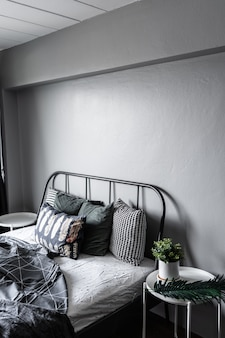 Bedroom corner with artificial plants in white ceramic marble pot on side table in modern scandinavian style