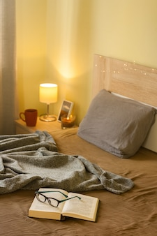 Bedroom cozy interior with blanket, open book with glasses and warm light
