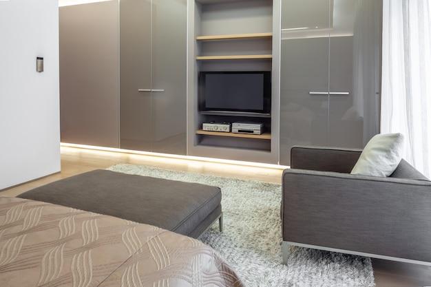 オーディオシステムとテレビ用の棚付きの作り付けのワードローブを備えたベッドルーム
