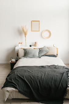 Спальня в скандинавском стиле минимализма. серые подушки на кровати. декор над кроватью