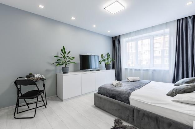큰 침대와 흰 벽이있는 작은 아파트의 침실
