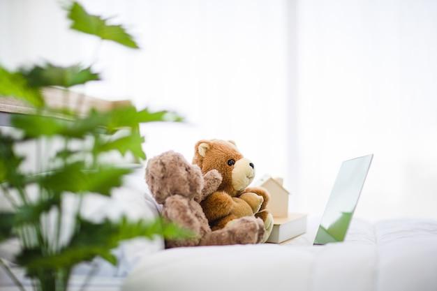 자연 컨셉의 침실은 친구처럼 침대에 두 개의 갈색 사랑스러운 푹신한 테디베어 장난감을 놓고 노트북을 보는 것을 즐깁니다.