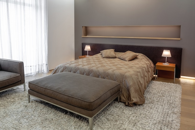Спальня в серо-коричневых тонах с двуспальными прикроватными светильниками и мягкой пуфиком.