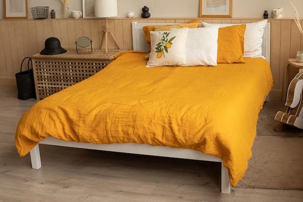 Bedroom interior bed in the interior, linen orange yellow bed linen . lemon print.