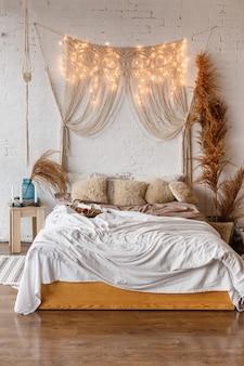 Дизайн интерьера спальни в стиле бохо с деревянной кроватью на фоне кирпичной стены с макраме и гирляндой