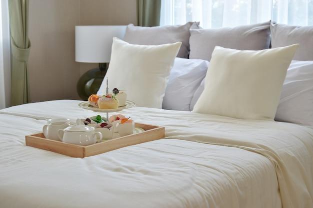 Bedroom interior design with decorative tea set and dessert on bed