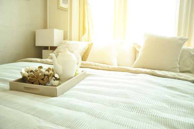 Bedroom interior design with luxury white pillows on bed and decorative table lamp.