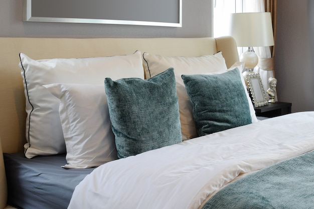 Bedroom interior design with white and green pillows on white bed