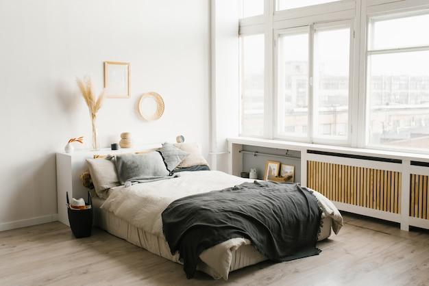 大きな窓を備えた白とグレーの配色のスカンジナビアのミニマリストスタイルの寝室のインテリア