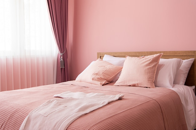 Bedroom interior of room with comfortable bed near pink wall
