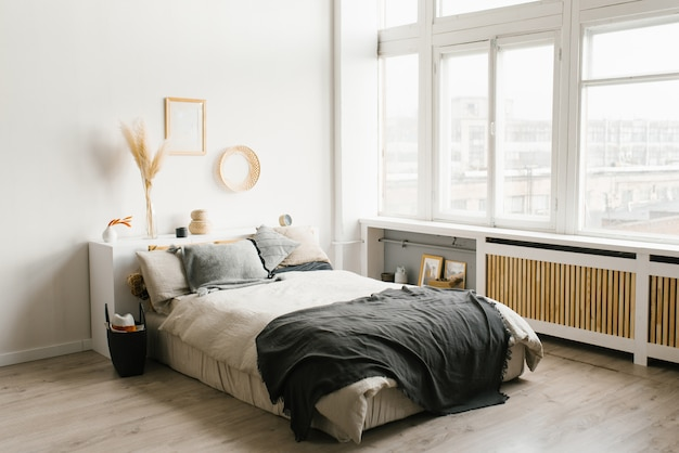 Bedroom interior in scandinavian minimalist style in white and gray color scheme with large windows