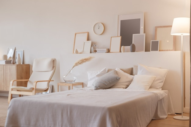 Bedroom interior with floor lamp and planty photoframes.