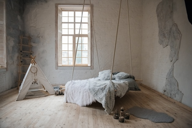 Bedroom in scandinavian style. suspended bed with blankets. wigwam.