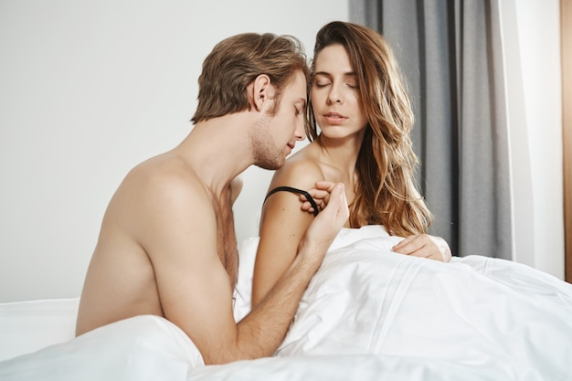 Bedroom shot of handsome bearded boyfriend kissing shoulder of girlfriend while being naked under blanket. passionate two people in relationship having foreplay in morning expressing love