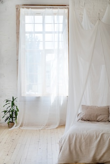 Bedroom in soft light colors with a wooden floor.
