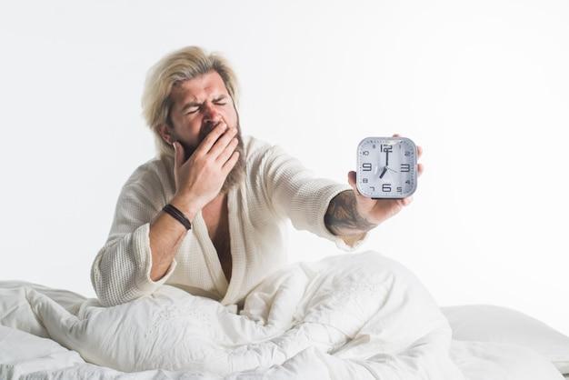 침실 시간. 각성. 아침. 알람 시계를 가진 남자입니다. 침대에서 수염 난된 남자입니다. 아침. 아침 루틴입니다. 알람 시계. 일어나 다. 낮잠 시간.