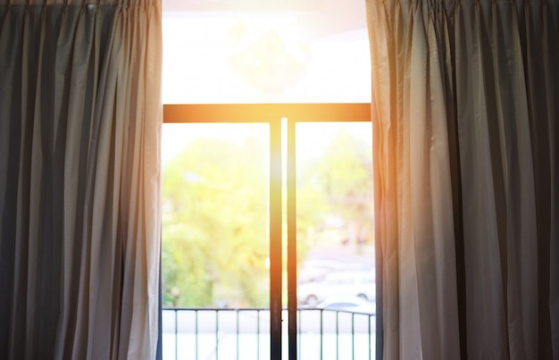 Bedroom window in the morning - sunlight through in room open curtains with balcony and nature tree on outside window