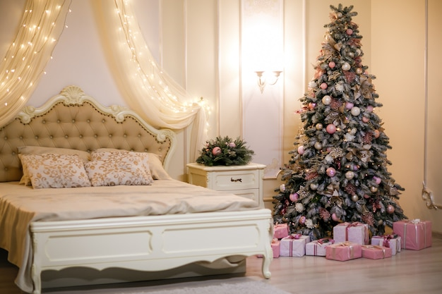 Bedroom with beige bed  and christmas tree. christmas interior.