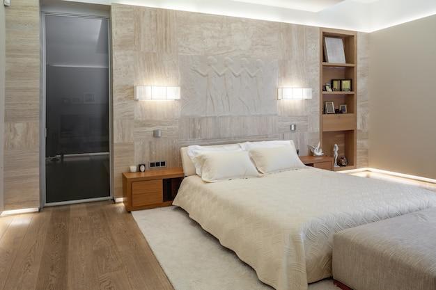 彫刻パネルと壁取り付け用燭台を備えた大理石の壁の近くにダブルベッドを備えたベッドルーム