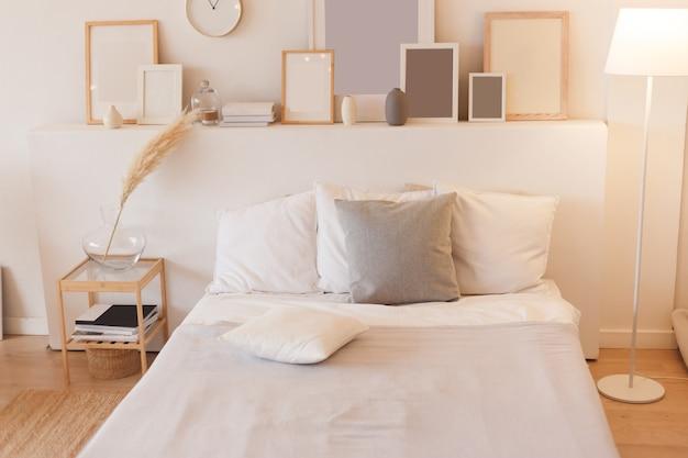 스위치가 켜진 플로어 램프와 사진 프레임이있는 침실.