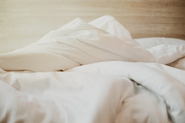 Спальня с белой кроватью, белым пуховым одеялом на кровати с деревянным изголовьем и солнечным светом.
