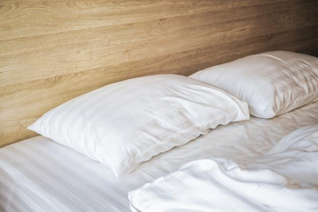 Спальня с белой кроватью, белыми двумя подушками, белым пуховым одеялом на кровати с деревянным изголовьем и солнечным светом.