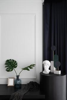 Рабочий уголок спальни украшен искусственным растением в стеклянной вазе и украшен минималистичной скульптурой в современном классическом стиле.