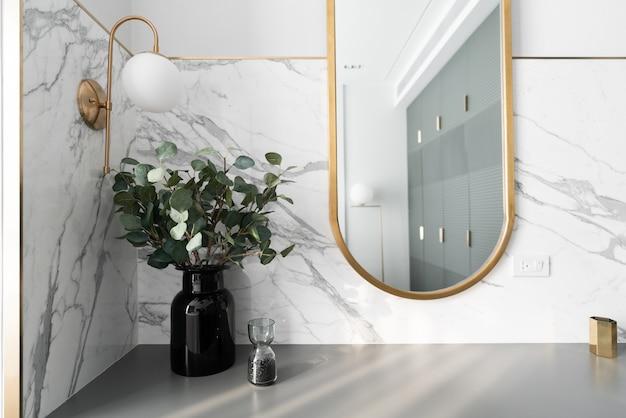 Рабочий уголок в спальне украшен золотым зеркалом из нержавеющей стали и искусственным растением в стеклянной вазе на рабочем столе, выкрашенном в серый цвет, с мраморной стеной