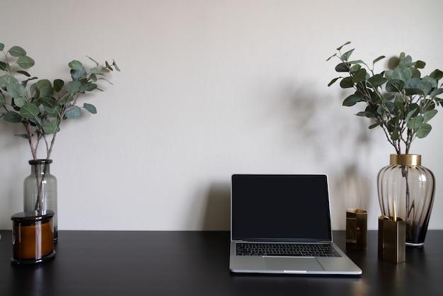 ラップトップの白いろうそくとベージュ色の壁の背景を持つ木製の作業テーブルのガラス花瓶に人工植物で飾られた寝室の作業コーナー