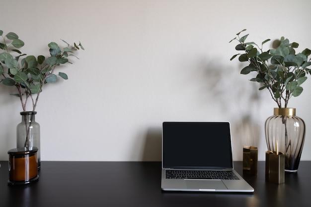 ラップトップの白いキャンドルとベージュの塗られた壁の背景を持つ木製の作業テーブルのガラス花瓶の人工植物で飾られた寝室の作業コーナー