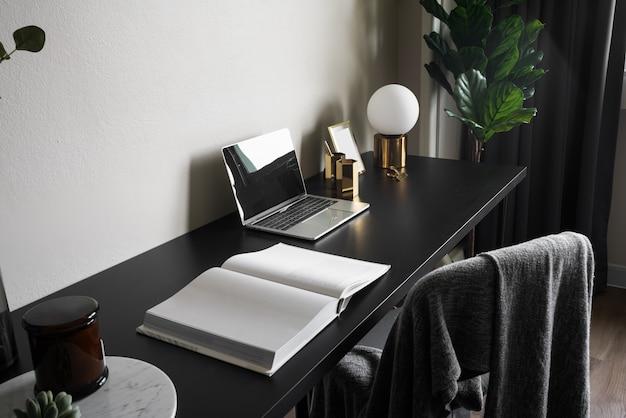 Рабочий уголок в спальне украшен ноутбуком с белыми свечами и искусственным растением в стеклянной вазе на деревянном рабочем столе с бежевой расписной стеной