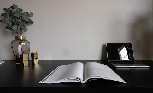 Спальня рабочий уголок с ноутбуком, белыми свечами и искусственным растением на черном деревянном рабочем столе.