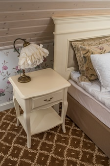 A bedside table with a lamp in the bedroom