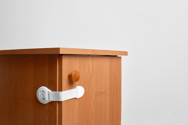 Bedside table wooden with baby proofing cabinet lock at home