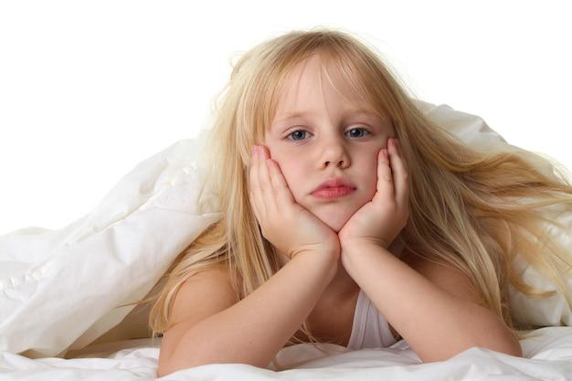 Перед сном - ребенок в постели с белым одеялом