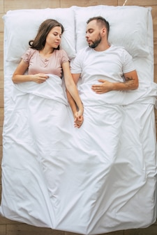Bedtime. the family are sleeping. beautiful young couple in love are lying on the big white bed and resting. husband and wife together in bed. top view photo