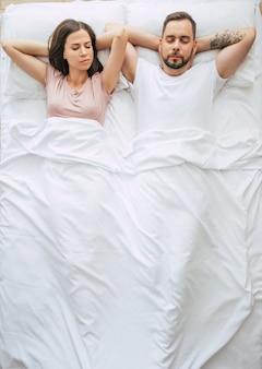 Перед сном. семья спит. красивая молодая влюбленная пара лежит на большой белой кровати и отдыхает. муж и жена вместе в постели. фото вид сверху