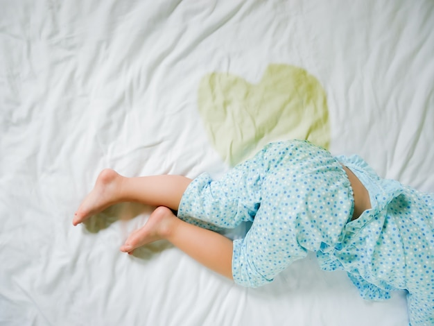 Bedwetting: child pee on a mattress,little girl feet and pee in bed sheet,child development concept ,selected focus at wet on the bed
