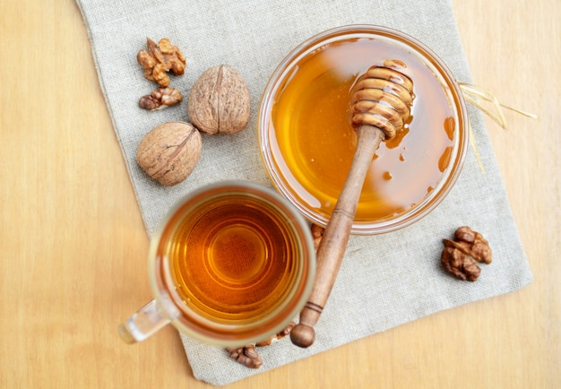 Bee honey and hot tea in glass cup with walnut snack on kitchen towel. overhead top view