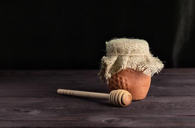 Пчелиный мед в глиняном горшочке на деревянном столе. деревянная лопатка для меда. вид сбоку, copyspace. здоровая пища.