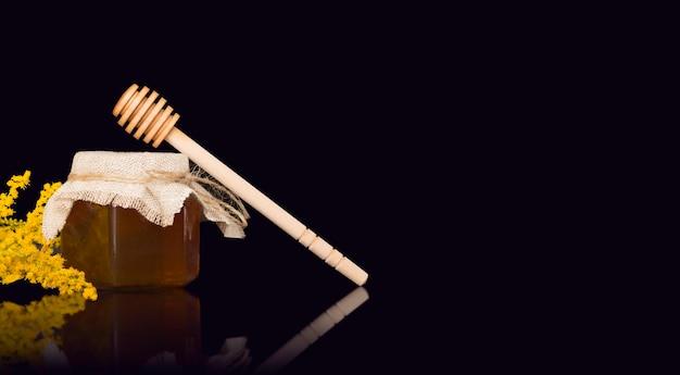 黄麻布、木のへら、黄色い花のカバーが付いているガラスの瓶の中のミツバチの蜂蜜