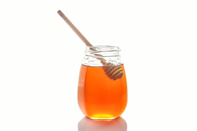 Мед пчелиный с деревянной ложкой для меда. изолированные