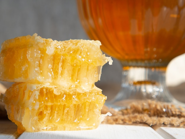 Bee honeycomb with honey close-up on an old wooden table